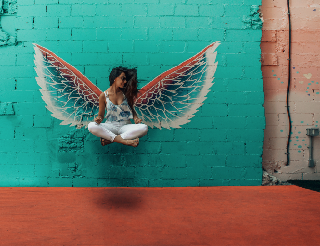 girl floating in air in front of wings painted on wall