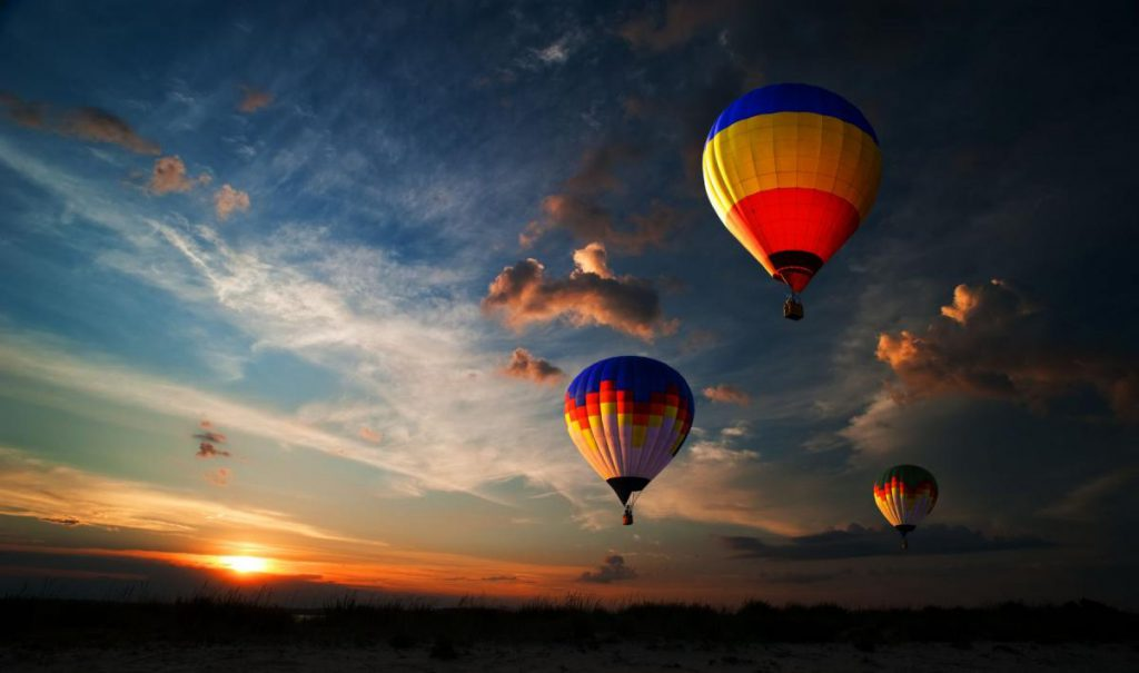 Several hot air balloons with sun in the horizon