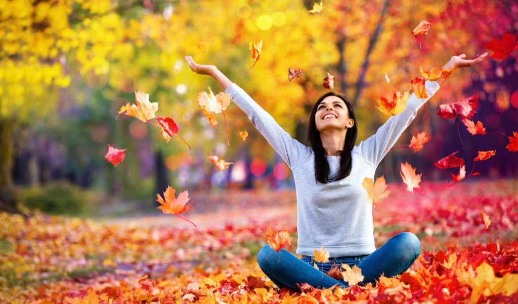 woman playing with autumn leaves on ground