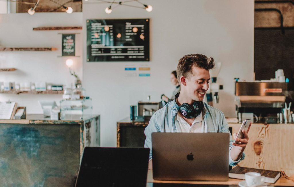Man using laptop and phone in coffee shop